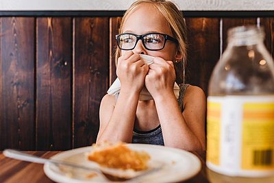Little girl eats and drinks at table in cafe restaurant - p1166m2124447 by Cavan Images