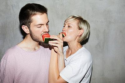 Couple feeding a melon  - p276m2115567 by plainpicture