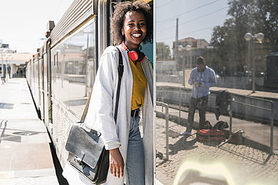 Happy young woman entering a train - p300m2155847 by Uwe Umstätter