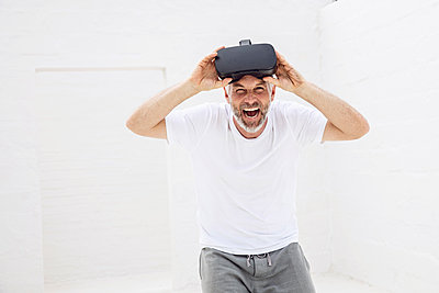 Mature man with VR goggles, looking at camera, laughing - p300m2156511 by Maya Claussen