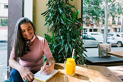 Smiling woman writing in diary while sitting with fresh juice at table in bar - p300m2226648 by Xavier Lorenzo
