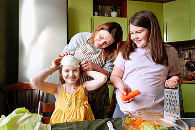 Playful mother and smiling daughters preparing food in kitchen at home - p300m2275114 by Ekaterina Yakunina