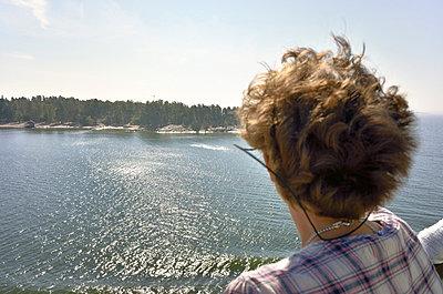 Woman looks at the Pihlajasaari island - p322m826548 by Kimmo von Lüders