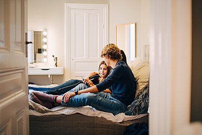 Male and female friends using technology while sitting on bed at home - p426m1555891 by Maskot