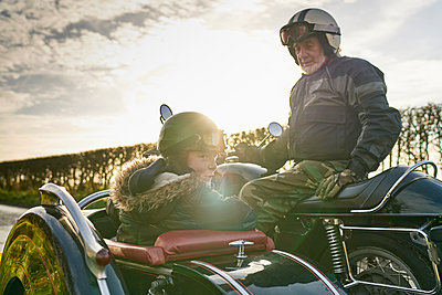 Senior man and grandson looking back from motorcycle and sidecar - p429m1226969 by GS Visuals