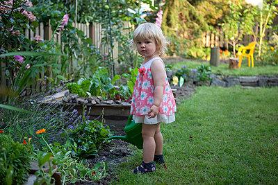 Kind gießt Blumen - p505m919151 von Iris Wolf