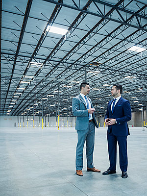 Businessmen talking in empty warehouse - p555m1305143 by Erik Isakson