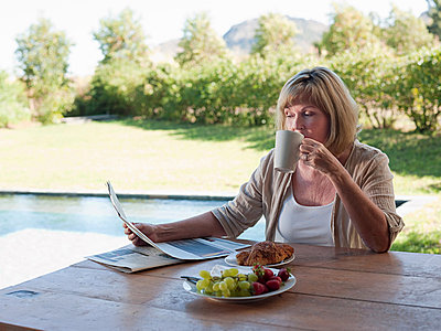 Woman outdoors, reading newspaper and drinking coffee - p9244473f by Image Source