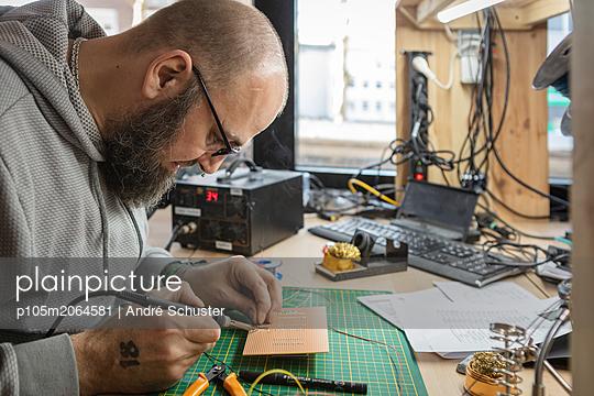 Elektriker lötet Bauteile auf eine Platine - p105m2064581 von André Schuster
