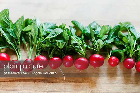 A row of radishes on cutting board - p1106m2182546 by Angela DeCenzo