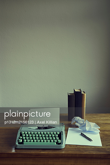 Typewriter with paper on table top - p1312m2156123 by Axel Killian