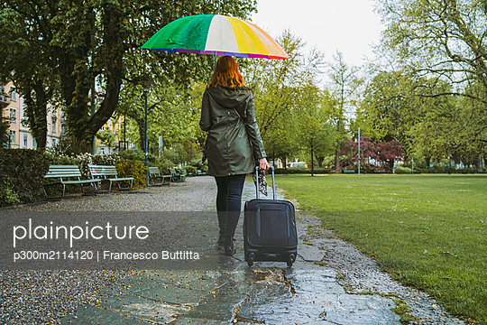 Young woman walking in city park on a rainy day - p300m2114120 von Francesco Buttitta