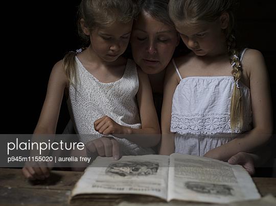 Mutter mit Töchtern und einem Märchenbuch  - p945m1155020 von aurelia frey