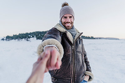 Smiling man holding woman's hand while standing in snow against clear sky - p300m2251277 by Eva Blanco