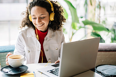 Smiling woman with laptop and headphones having coffee at cafe - p300m2282184 by COROIMAGE