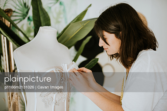 Young fashion designer making a wedding dress - p1166m2131026 by Cavan Images