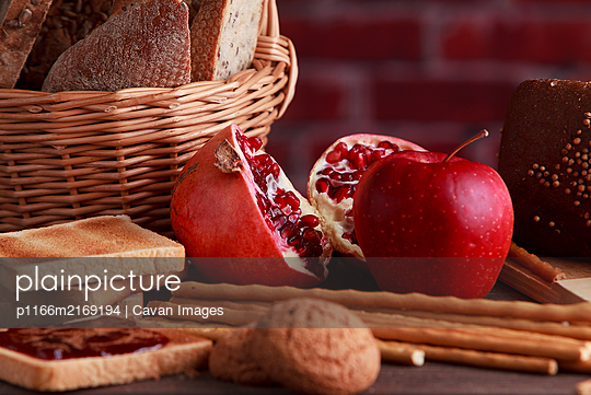 Different buns of fresh bread and spikelets of wheat on a brown vintage background - p1166m2169194 by Cavan Images