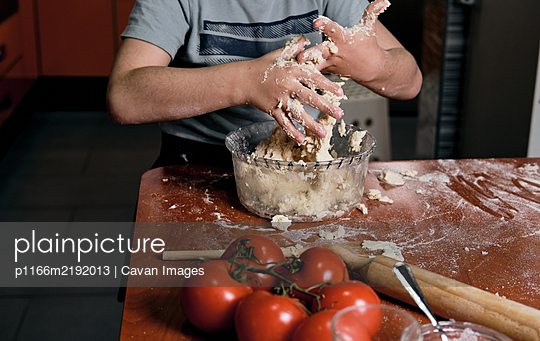 zenithal view of child preparing pizza dough to make at home - p1166m2192013 by Cavan Images