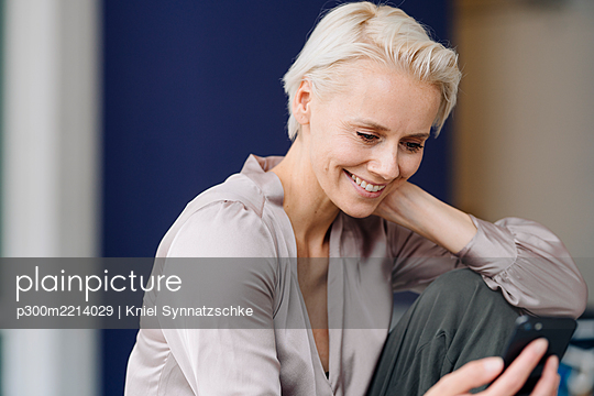Close-up of smiling female entrepreneur using mobile phone while sitting in office - p300m2214029 by Kniel Synnatzschke