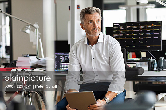 Mature businessman with digital tablet looking away while sitting at office - p300m2257074 by Peter Scholl
