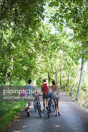 Three friends with mountain bikes in forest - p31227306f by Plattform photography