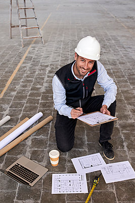 Smiling male architect holding site plan while kneeling on floor in building - p300m2243428 by Veam
