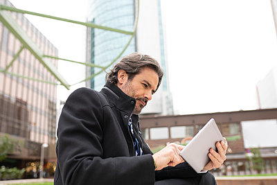 Concentrated male professional using digital tablet in office park - p300m2275317 by Jose Carlos Ichiro