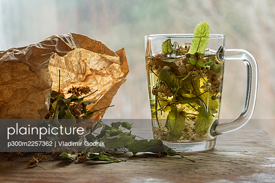 Dried linden leaves in paper bag by glass of lime tea on wooden cutting board - p300m2257362 by Vladimir Godnik