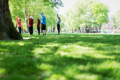 Active seniors exercising, practicing yoga in park - p1023m2034057 by Tom Merton