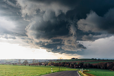 Stormy atmosphere over empty country road - p300m1494834 by Jana Mänz