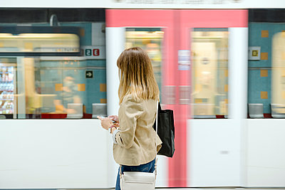 Woman in casual clothing using smart phone by subway train during COVID-19 - p300m2264606 by Albert Martínez