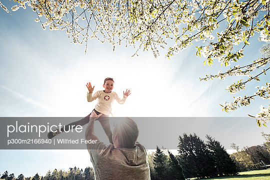 Father throwing son in air - p300m2166940 by Wilfried Feder