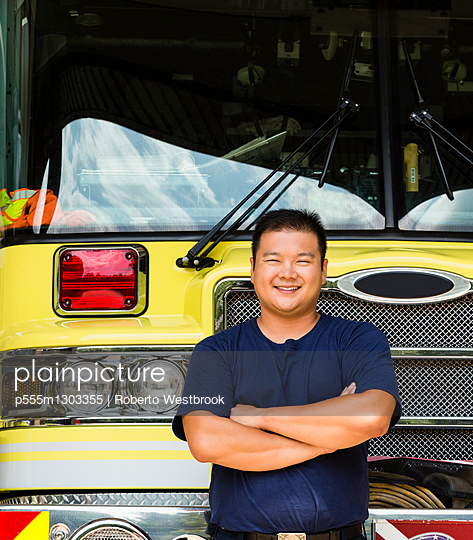 Smiling Chinese fireman posing with fire truck
