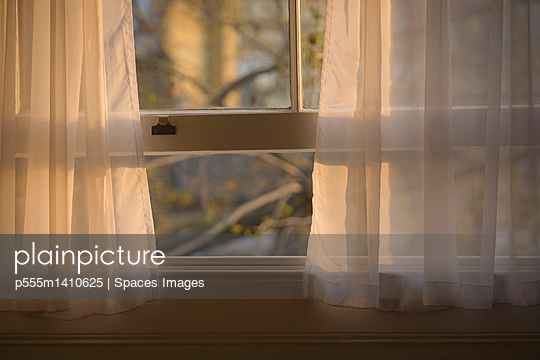 Sheer curtains in open window - p555m1410625 by Spaces Images