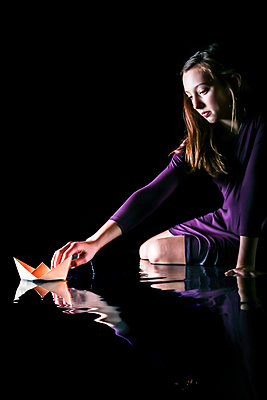 Teenage girl playing with paper boat - p1019m1525617 by Stephen Carroll