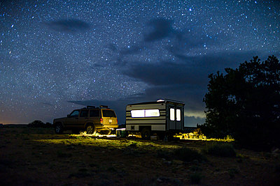 Car and illuminated travel trailer against star field - p1166m1474577 by Cavan Images