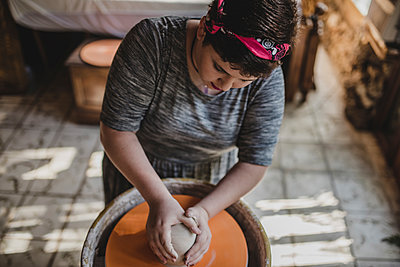 High angle view of female potter making clay pot at pottery - p1166m1512986 by Cavan Images