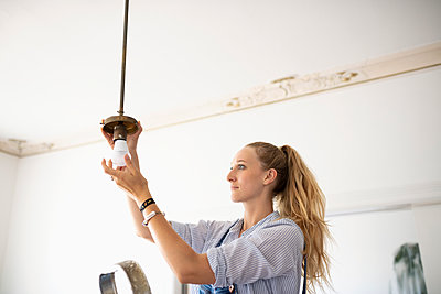 DIY woman changing light fixture - p1192m2016790 by Hero Images