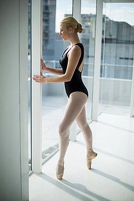 Ballerina standing against glass window - p1315m1230735 by Wavebreak