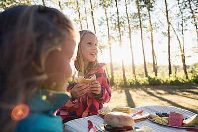 Sisters having dinner at an outdoor kids table. - p328m784074f by Hero Images