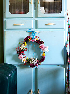 Floral wreath on blue kitchen cabinet;  Isle of Wight home;  UK - p349m920100 by Rachel Whiting