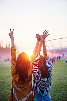Two young women with hands raised making peace sign at Holi Festival, rear view - p429m2019061 by Gpointstudio
