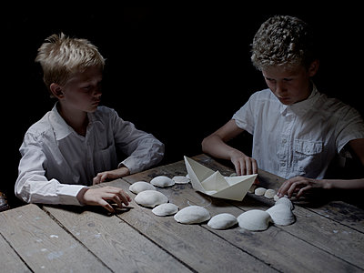 Two boys playing with shells and paper boat - p945m1154603 by aurelia frey