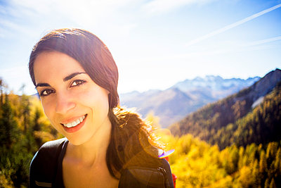 Happy young brunette woman hiking in Italian mountains - p968m1028401 by Roberto Pastrovicchio