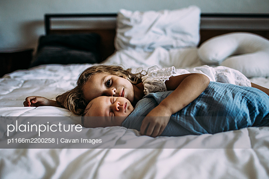 portrait of young girl snuggling newborn brother - p1166m2200258 by Cavan Images