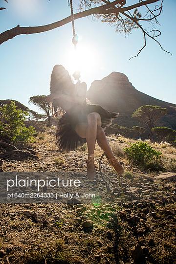 Brunette woman swings under tree - p1640m2264333 by Holly & John