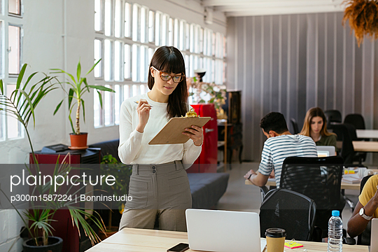 Woman with clipboard among colleagues in office - p300m1587224 von Bonninstudio