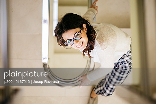 Smiling young woman on staircase looking up - p300m2167213 von Josep Rovirosa