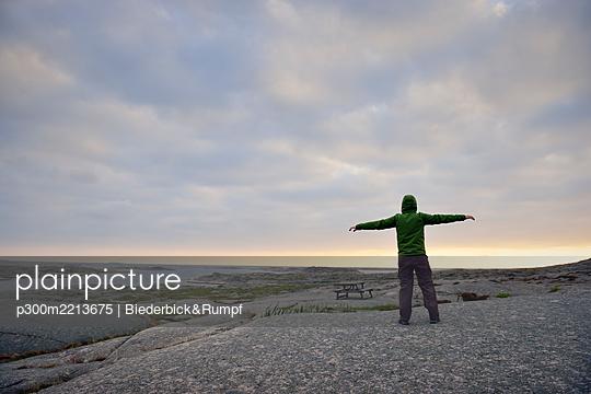 Sweden, Kungshamn, Young man at skerry coast - p300m2213675 by Biederbick&Rumpf