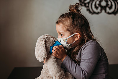 Close up of young girl with mask on kissing masked stuffed animal - p1166m2207790 by Cavan Images